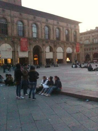 Gente in piazza Maggiore all'alba (foto di Rodolfo Ruè da Twitter)