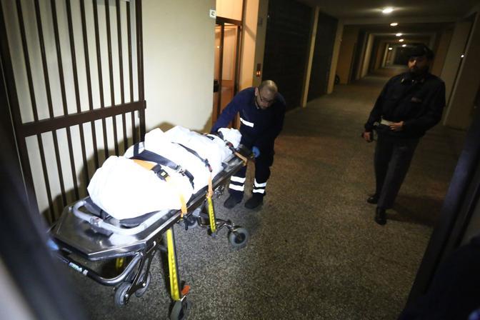 Il cadavere della signora 80enne viene portato fuori di casa