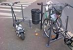 Parcheggio per tutti - Non solo biciclette. Tra i mezzi a zero impatto ambientale qualcuno sceglie il monopattino, magari con l'aggiunta di un motorino elettrico per girare in città. E dovrà pur parcheggiarlo, da qualche parte (con super catena agganciata al palo).
