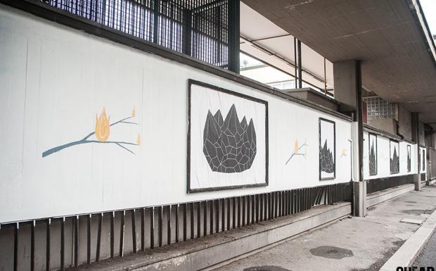 Il muro dell'Autostazione invaso dalla street art - Il muro di cinta dell'Autostazione è stato  nel corso del tempo protagonista di diversi interventi curati da Cheap già a partire dalla prima edizione del festival. I 250 metri quadri  di superficie scanditi da 43 disegni rappresentano in effetti una sintesi visiva efficace della tipologia di spazi su cui Cheap interviene, comprendendo al contempo superficie muraria e spazi affissivi in disuso. Proprio qui, tra le zone di maggior passaggio veicolare della città, l'artista Andreco ha realizzato un intervento site specific a tecnica mista con evidenti rimandi alle principali cause dell'inquinamento antropico. Emissions – questo il titolo – è la seconda tappa di Climate, macro progetto itinerante sui cambiamenti climatici inaugurato a Parigi in concomitanza con COP21, tL'ultima conferenza delle Nazioni Unite sul tema. Concepita con uno sviluppo narrativo che procede per simboli, l'opera si evolve su due filoni tematici che si intersecano, identificabili nel doppio binomio support e tecnica: da un lato la pittura su muro, dall'altro i poster affissi sui billboard. Il murales va letto partendo da viale Masini angolo via Capo di Lucca andando nella direzione della stazione dei treni. I primi due blocchi di parete, scandita dalle colonne portanti della pensilina, sono occupati da una nebulosa ascendente che fa riferimento agli inquinanti presenti nei gas di scarico prodotti dal traffico veicolare. Nel terzo blocco, il focus è invece posto sugli inquinanti che generano l'effetto serra. Successivamente, l'attenzione si sposta sull'inquinamento nel ciclo delle acque. Nei blocchi seguenti, appaiono funzioni che fanno riferimento alla percentuale di CO2 in atmosfera, le curve mostrano in maniera simbolica il superamento del limite consigliato per limitare i cambiamenti climatici di 350 ppm (parti per milione) di CO2. A seguire altre funzioni fanno riferimento all'innalzamento delle temperature, le funzioni diventano quasi diseg