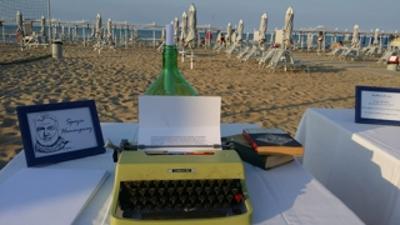 """Come Hemingway, a Riccione -  Per due ore spegniamo tablet o smartphone. Torna la macchina per scrivere. In un posto insolito: sulla spiaggia di Marano a Riccione. Ogni domenica, fino al 25 settembre, il Mojito Beach mette a disposizione per due ore (17.30 – 19.30) lo «Spazio Hemingway». Un luogo aperto a chiunque vuole raccontare, fermare su una pagina il suo rapporto, i sentimenti o i ricordi che lo legano al mare. L'unico limite, molto lontano dai 140 caratteri di un tweet, è quello di limitarsi a una pagina, un foglio, ovvero 30 righe. Il testo, magari accompagnato da un titolo, una firma e un recapito per tenersi in contatto con il """"Mojito Beach"""" e gli altri scrittori di mare, può essere lasciato in una grande bottiglia di vetro, appoggiata vicino alle macchine da scrivere. I racconti più curiosi e emozionanti saranno postati sulla pagina Facebook del """"Mojito"""". A fine settembre i tre migliori saranno premiati durante la cena """"Scrittura di Mare"""", organizzata nel ristorante dello stabilimento """"La Mar"""" e di cui i tre autori saranno ospiti d'onore."""