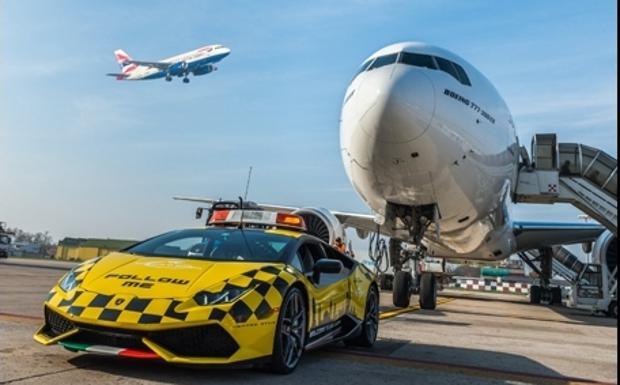 """Lambo «Follow Me» al Marconi -  C'è una Lamborghini all'Aeroporto Marconi di Bologna come auto «follow me» per gli aerei. È una Huracán che fino a gennaio 2017 guiderà gli aeromobili verso il piazzale di sosta e la via di rullaggio. La Huracán Follow Me, supersportiva dal motore V10 aspirato e da 610 CV, è caratterizzata da una speciale livrea disegnata dal Centro Stile Lamborghini a quadretti neri su carrozzeria gialla, e inaugura la nuova livrea che sarà prevista per i mezzi operativi che si muovono nelle aree di manovra degli aeromobili. Completano gli esterni una grafica che raffigura lo skyline della città di Bologna sulle portiere e il tricolore sullo spoiler anteriore. La vettura è inoltre dotata dell'allestimento tipico dei mezzi """"Follow Me"""": barra segnaletica sul tetto, lampeggianti di segnalazione e radio collegata con la Torre di Controllo."""